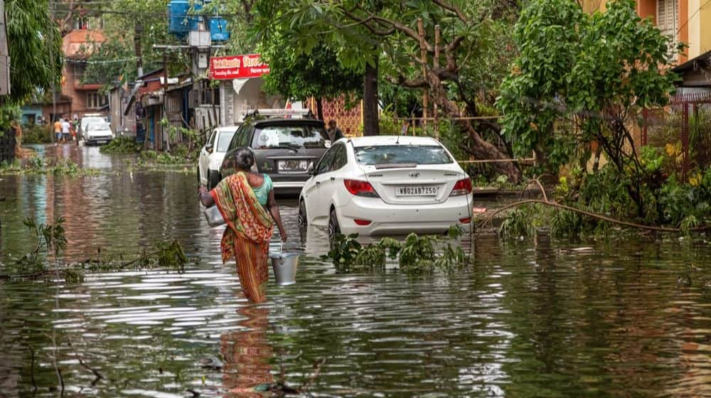 Woman Carrying Drinking Water through Water logged | Mumbai Spared, But Heavy Storms Ahead in 2020 | Featured