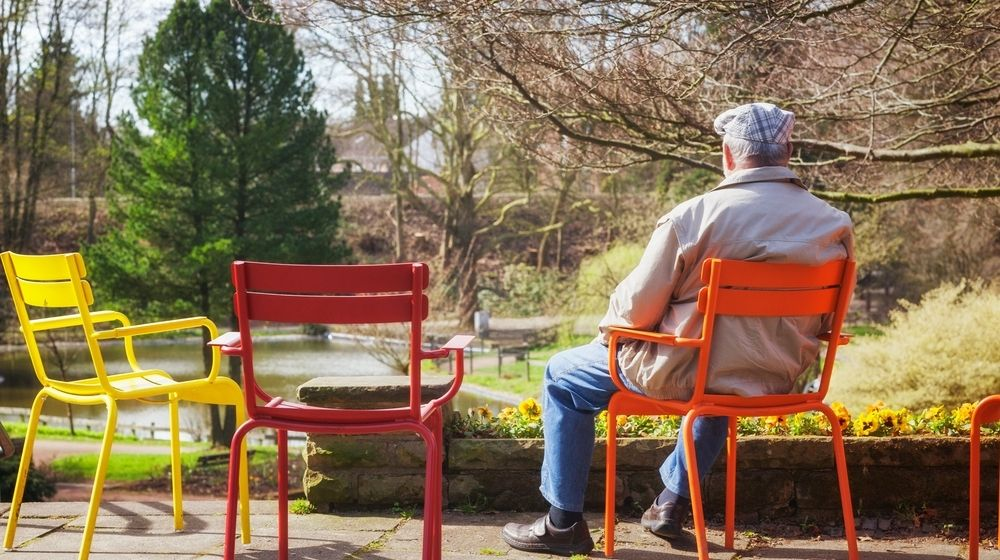 Rear View of Elderly Man Sitting on Chair in Early Spring Park | More and More Americans Are Being Offered to Retire Early Due to the COVID-19 Pandemic | Featured