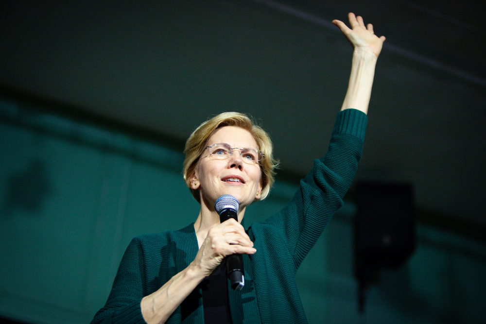 Elizabeth Warren speaking at a campain with one hand raised-Sanders and Warren at Risk of Being Excluded from the Biden Administration's Senior Ranks-ss-Featured
