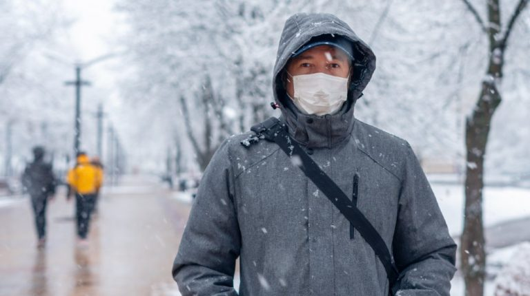 Portrait of a Man Wearing a Medical Protective Mask on his Face in Winter   Brace Yourselves: COVID-19 Winter Is Coming   Featured