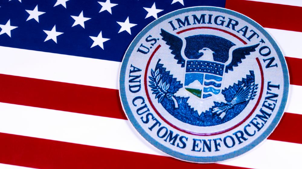 The symbol of US Immigration and Customs Enforcement portrayed with the US flag-Gang Members Deported-ss-featured
