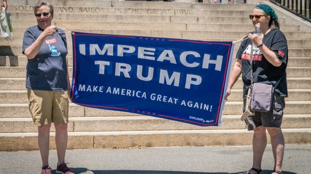 "Two women holding an ""impeach Trump"" banner-Impeachment- House of Democrats Pushing for 25th Amendment invocation-ss-featured"