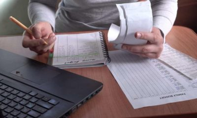 Person doing finances-Household Debt Rises to $14.6 Trillion Due to Increase in Mortgage Loans-ss-Featured