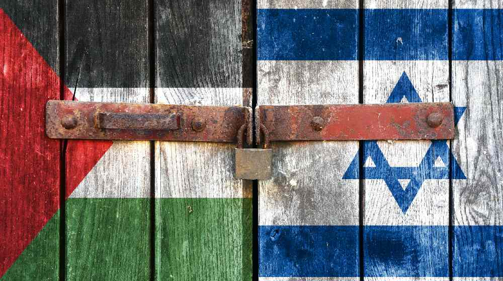 Palestinian flag with the Israeli flag on the background of old locked doors   Israeli Official Vows To Destroy Hamas For Its Rocket Attacks   Featured