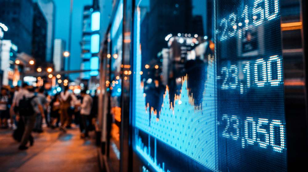 Display of Stock market quotes with city scene reflect on glass   7 Reasons Stock Exchanges Have Performed, So Well, Recently!   featured