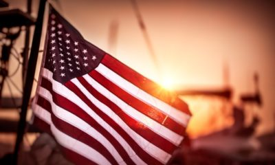 Flag of United States of America flutters in the winds in mild sunset light | 5 Priorities For America To Address | featured