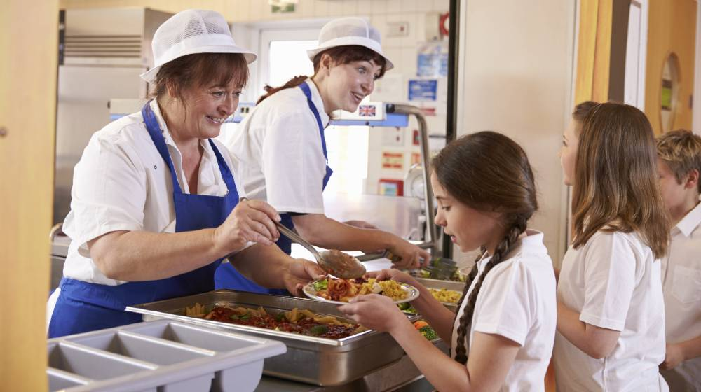 Two women serving food to a girl in a school cafeteria queue | Supply Chain Shortages Will Affect School Cafeterias | featured
