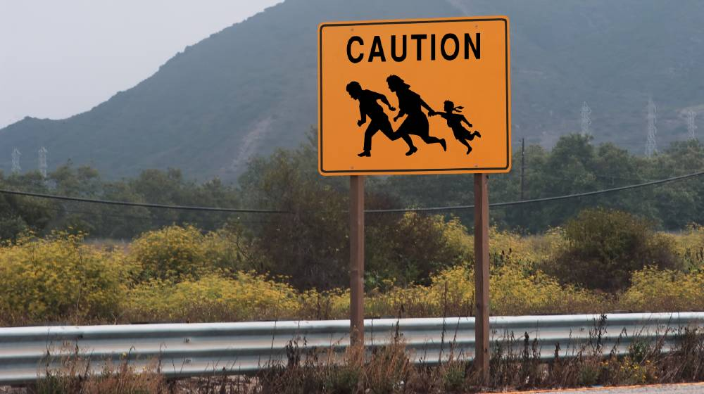 highway sign showing family crossing | Abbott Orders Texas National Guard To Arrest Migrants | featured