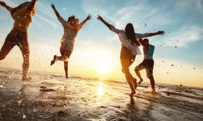 Four happy friends at sunset beach party runs to water | Are These The Keys To A Happier Life | featured