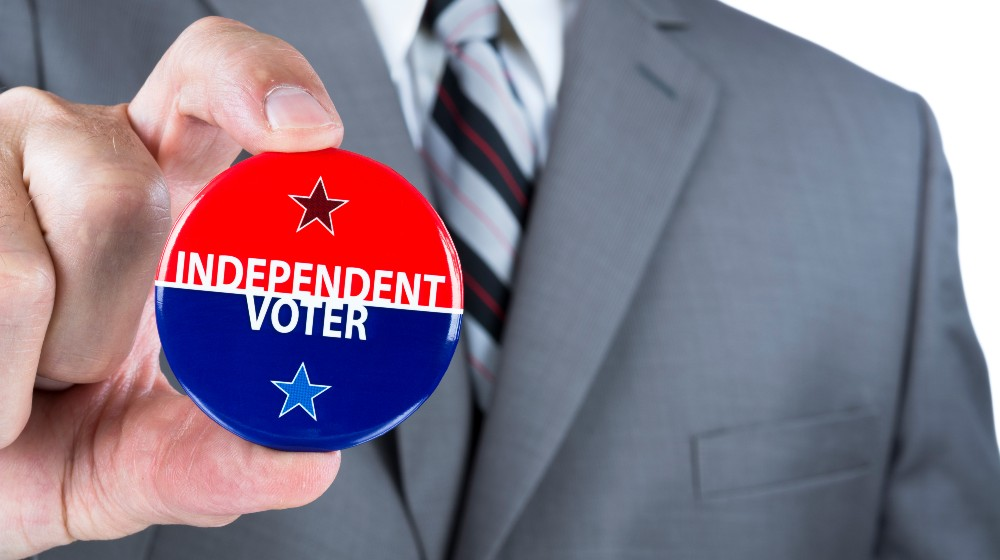 A man in a business suit holds out a political independent voter pin during elections | Independent Voters Are Dumping Joe Biden In Large Numbers | featured